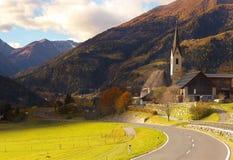 一条路和圣玛丽亚教会的看法在Obervellach村庄, Austr 免版税库存照片