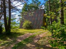 一条路在导致游人的一个小的房子的森林里在站立在岸的石板屋顶下大 免版税库存图片
