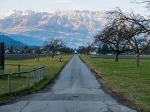 一条路在带领往山的一个小村庄 库存图片