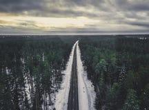 一条路的寄生虫摄影在森林之间的在冬天-葡萄酒lo 免版税库存图片