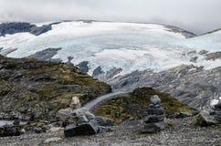 一条路的看法从Dalsnibba观点视图的巨大的冰川在背景和岩层中在前景 免版税库存照片