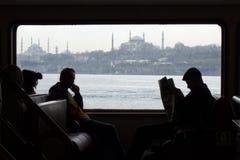 一条轮渡的通勤者在有hagia索非亚和苏丹艾美清真寺的伊斯坦布尔 免版税库存照片