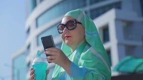 一条轻的围巾和太阳镜的一名年轻回教妇女以一个现代大厦为背景 股票录像