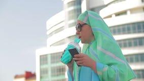 一条轻的围巾和太阳镜的一名年轻回教妇女以一个现代大厦为背景 影视素材