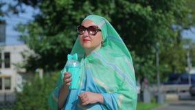 一条轻的围巾和太阳镜的一名年轻回教妇女在公园喝咖啡 股票录像