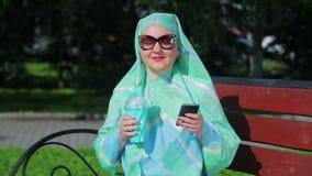 一条轻的围巾的一名年轻回教妇女和太阳镜坐一条长凳在公园和饮用的咖啡和谈 股票录像