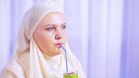 一条轻的围巾的一名年轻回教妇女喝果子圆滑的人和微笑 影视素材