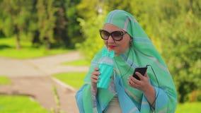 一条轻的围巾的一名年轻回教妇女在公园在有耳机的信使喝咖啡并且谈话 股票录像