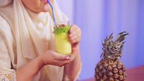 一条轻的围巾的一名年轻回教妇女拿着与果子圆滑的人的一块玻璃在她的手和饮料上从秸杆 股票录像