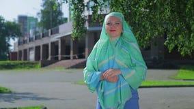 一条轻的围巾的年轻回教妇女在公园 影视素材