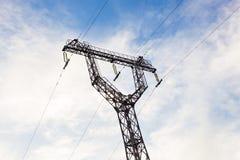 一条输电线的定向塔与蓝天的 免版税库存图片