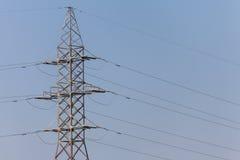 一条输电线的杆反对蓝色高昂的电压力量的 库存照片