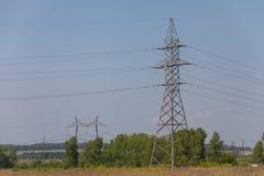 一条输电线的杆反对蓝色高昂的电压力量的 免版税图库摄影