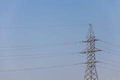 一条输电线的杆反对蓝色高昂的电压力量的 免版税库存图片