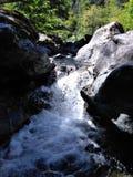 一条迅速流动的小河的另一个看法被紧贴在山之间 免版税库存照片