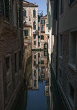 一条运河在威尼斯-老大厦和他们的反射 库存图片