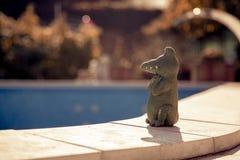 一条逗人喜爱的鳄鱼的小小雕象在一个空的游泳池的边缘的 秋天概念查出的白色 免版税库存照片