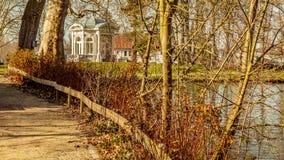 一条道路有茶圆顶的或Gloriette的美丽的景色在一个池塘旁边的在背景中 库存照片