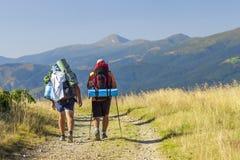 一条道路的两个远足者游人在山 免版税库存图片