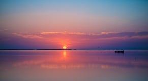 一条遥远的小船在美丽如画的日落背景的安静的海 免版税库存照片
