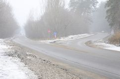一条郊区柏油路的交叉路在bli期间的冬天 免版税库存图片