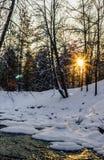 一条部分冻河的镇静冬天照片有发光的太阳的  库存图片