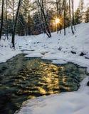 一条部分冻河的镇静冬天照片有发光的太阳的  库存照片