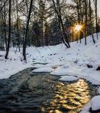 一条部分冻河的镇静冬天照片有发光的太阳的  免版税库存照片