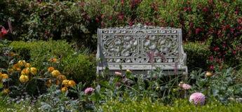 一条金属长凳在花床上 免版税库存照片