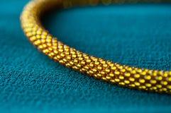 一条金黄项链的片段在绿色背景的 免版税图库摄影