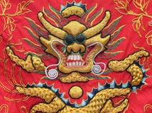 一条金黄龙的挂毯在红色丝绸背景的 免版税库存图片