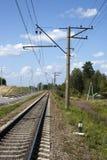 一条铁路在与白色云彩的蓝天下  库存图片