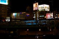 一条铁路的夜视图与通过的火车和有启发性商业的签到新宿,东京,日本 库存图片