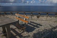一条长凳和一张桌由海边,马德拉岛,葡萄牙 免版税库存图片