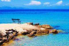 一条长凳有一个看法在Ammoudi村庄,扎金索斯州海岛 图库摄影