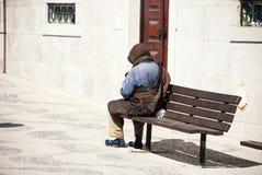 一条长凳的一个无家可归的人在里斯本,葡萄牙 库存图片