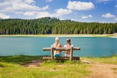 一条长凳的两个女孩在湖附近 库存照片