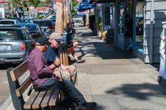 一条长凳的两个老年人白种人男性朋友在巴波亚海岛购物的区  库存图片