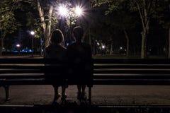 一条长凳的两名妇女在晚上 免版税库存照片