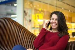 一条长凳的俏丽的妇女在购物中心 图库摄影