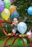 一条长凳的十几岁的女孩与气球 免版税库存照片
