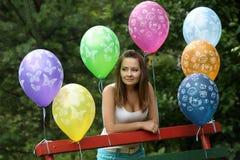 一条长凳的十几岁的女孩与气球 库存照片