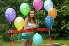 一条长凳的十几岁的女孩与气球 免版税图库摄影