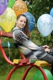 一条长凳的十几岁的女孩与气球 库存图片