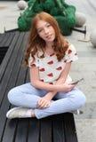 一条长凳的女孩与电话 图库摄影