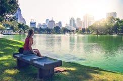 一条长凳的女孩在公园在曼谷 免版税库存照片