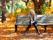 一条长凳的女孩在公园 免版税库存照片