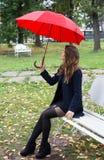 一条长凳的女孩在城市公园 库存照片
