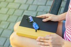 一条长凳的女孩在有一本书和玻璃的公园在她膝部 读一本书的学生在公园 免版税库存图片