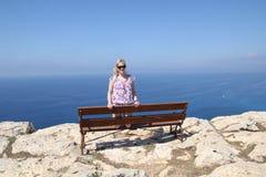 一条长凳的女孩在格雷科的海角 库存照片